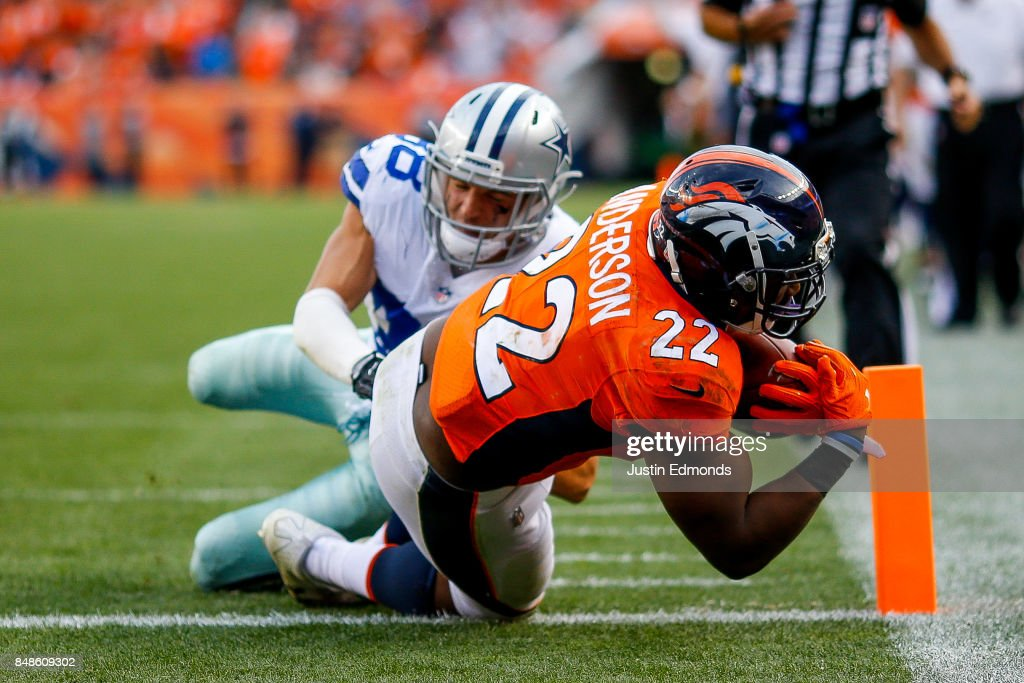 Running back C.J. Anderson #22 of the Denver Broncos rushes past strong safety Jeff Heath #38 of the Dallas Cowboys for a third quarter touchdown at Sports Authority Field at Mile High on September 17, 2017 in Denver, Colorado.