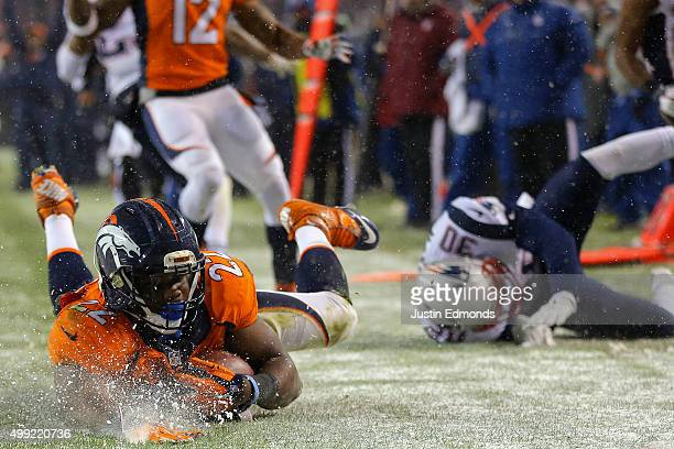 Running back CJ Anderson of the Denver Broncos scores a fourth quarter touchdown past cornerback Duron Harmon of the New England Patriots at Sports...