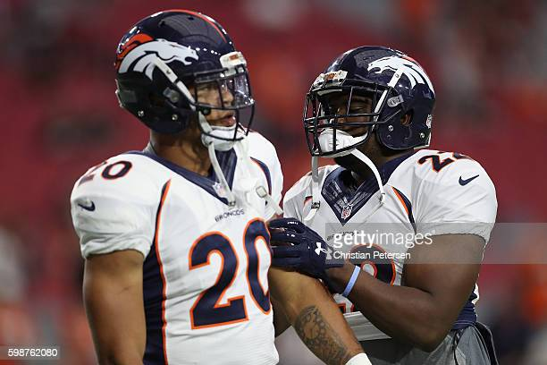 Running back CJ Anderson of the Denver Broncos talks with running back Devontae Booker during the preseaon NFL game against the Arizona Cardinals at...