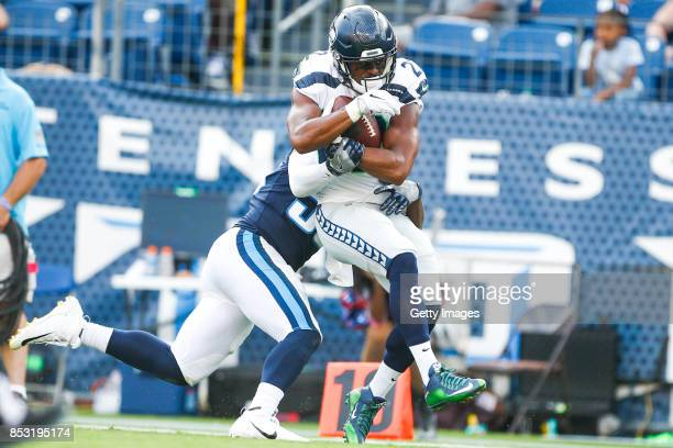 Running Back CJ Prosise of the Seattle Seahawks makes a catch against Linebacker Jayon Brown of the Tennessee Titans at Nissan Stadium on September...