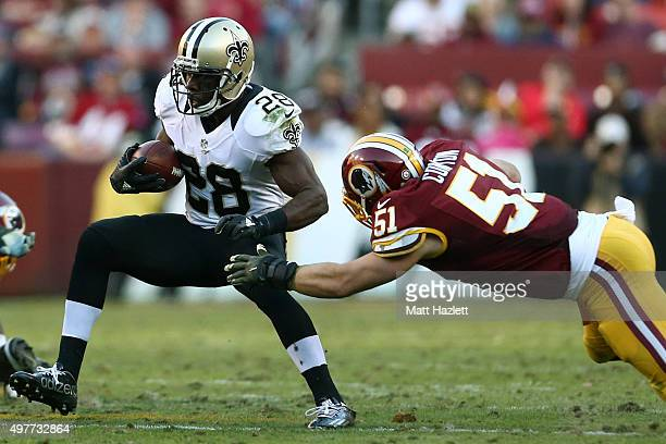 Running back CJ Spiller of the New Orleans Saints rushes against inside linebacker Will Compton of the Washington Redskins in the fourth quarter at...