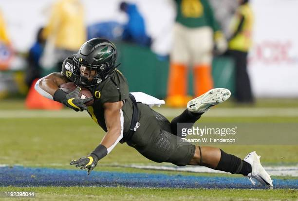 Running back CJ Verdell of the Oregon Ducks dives forward for a first down against the Utah Utes during the first half of the Pac-12 Championship...
