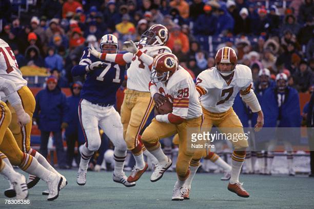 Running back Clarence Harmon takes a handoff from quarter Joe Theismann of the Washington Redskins against the Buffalo Bills on December 4 1977 at...