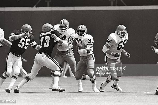 Running back Cleo Miller of the Cleveland Browns runs the football as offensive linemen Tom DeLeone and Henry Sheppard block against linebacker Jim...