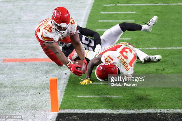 Running back Clyde Edwards-Helaire of the Kansas City Chiefs dives into the end zone for a touchdown past the defense of strong safety Jeff Heath of...