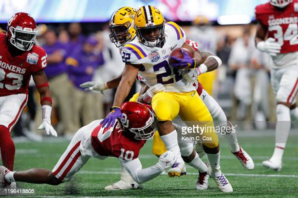 Running back Clyde EdwardsHelaire of the LSU Tigers carries the ball over wide receiver Theo Wease of the Oklahoma Sooners during the ChickfilA Peach...