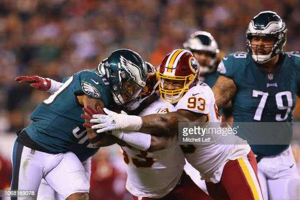 Running back Corey Clement of the Philadelphia Eagles runs with the ball and is tackled by linebacker Zach Brown and defensive end Jonathan Allen of...