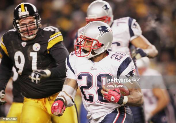 Running back Corey Dillon of the New England Patriots looks for running room while chased by defensive end Aaron Smith of the Pittsburgh Steelers in...
