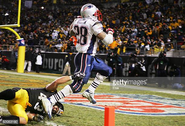 Running back Corey Dillon of the New England Patriots runs through the tackle attempt by safety Troy Polamalu of the Pittsburgh Steelers to score a...