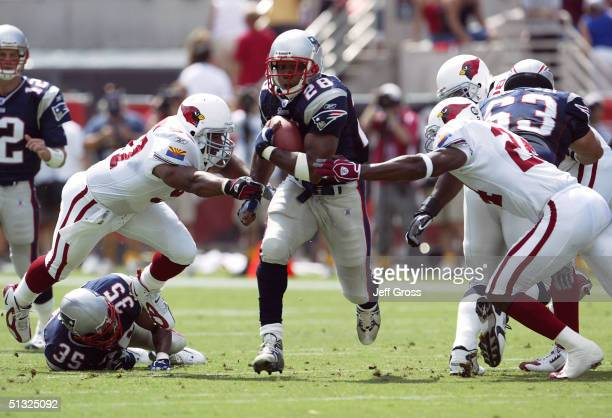 Running back Corey Dillon of the New England Patriots runs with the football between Ronald McKinnon and Adrian Wilson of the Arizona Cardinals at...