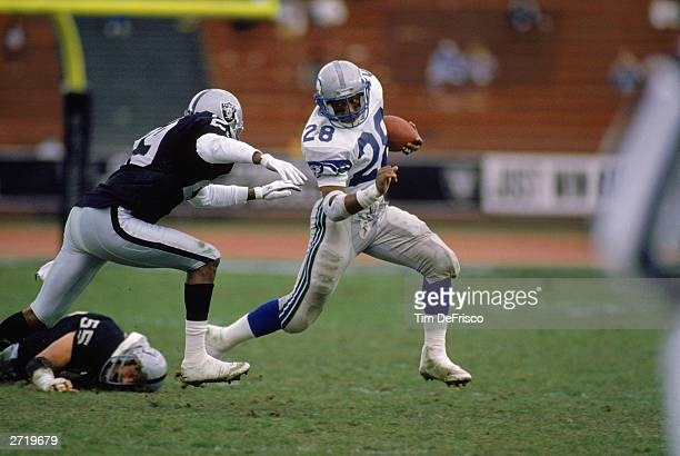 Running back Curt Warner of the Seattle Seahawks runs around a Los Angeles Raiders defender at the Los Angeles Coliseum on December 18, 1988 in Los...