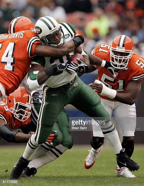 Running back Curtis Martin of the New York Jets starts off the game running as linebacker Andra Davis of the Cleveland Browns tackles him in the...