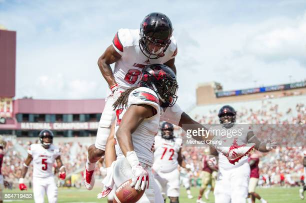 Running back Dae Williams of the Louisville Cardinals celebrates with wide receiver Dez Fitzpatrick of the Louisville Cardinals after scoring a...