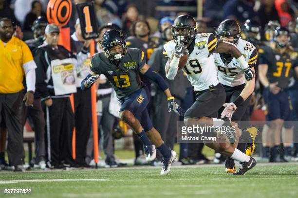 Running back Daetrich Harrington of the Appalachian State Mountaineers runs the ball by defensive back Ka'dar Hollman of the Toledo Rockets on...