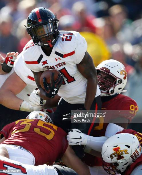 Running back Da'Leon Ward of the Texas Tech Red Raiders is tackled by linebacker Jake Hummel of the Iowa State Cyclones, and defensive lineman Jamahl...