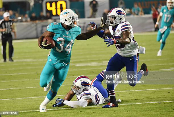 Running back Damien Williams of the Miami Dolphins carries the ball as Preston Brown and Da'Norris Searcy of the Buffalo Bills chase during a NFL...