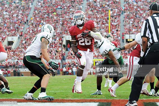 Running back Damien Williams of the Oklahoma Sooners scores a first half touchdown despite the defensive efforts of defensive end Terrance Lloyd and...