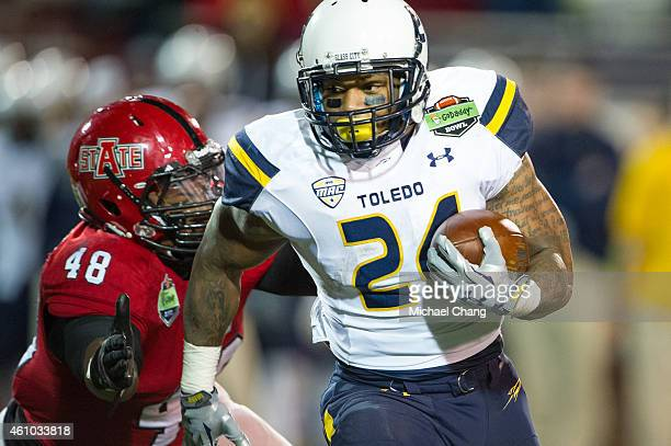 Running back Damion JonesMoore of the Toledo Rockets runs the ball past linebacker Qushaun Lee of the Arkansas State Red Wolves on January 4 2015 at...