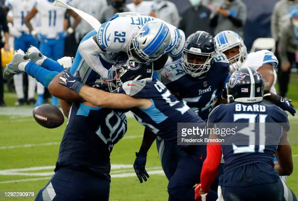 Running back D'Andre Swift of the Detroit Lions looses the football on a hit by inside linebacker Will Compton of the Tennessee Titans recovered by...