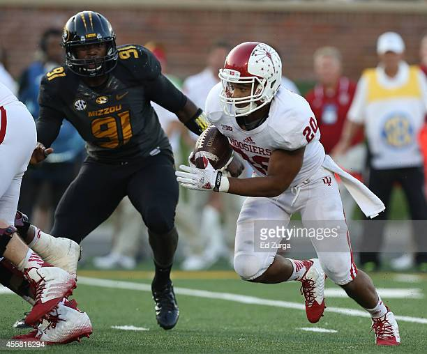 Running back D'Angelo Roberts of the Indiana Hoosiers looks for a hole to run through as he gets past Charles Harris of the Missouri Tigers in the...