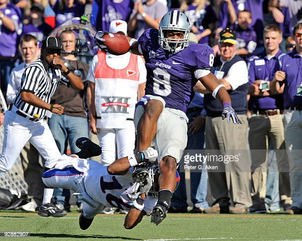 Running back Daniel Thomas of the Kansas State Wildcats tries to break through the tackle of defensive back Chris Harris of the Kansas Jayhawks in...