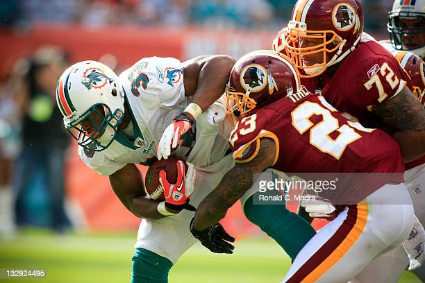 Running back Daniel Thomas of the Miami Dolphins carries the ball and is tackled by DeAngelo Hall and Stephen Bowen of the Washington Redskins during...