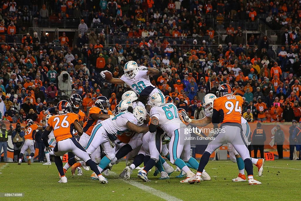 Running back Daniel Thomas #30 of the Miami Dolphins leaps and extends the ball over the goal line for a 2-point conversion late in the fourth quarter of a game against the Denver Broncos at Sports Authority Field at Mile High on November 23, 2014 in Denver, Colorado.