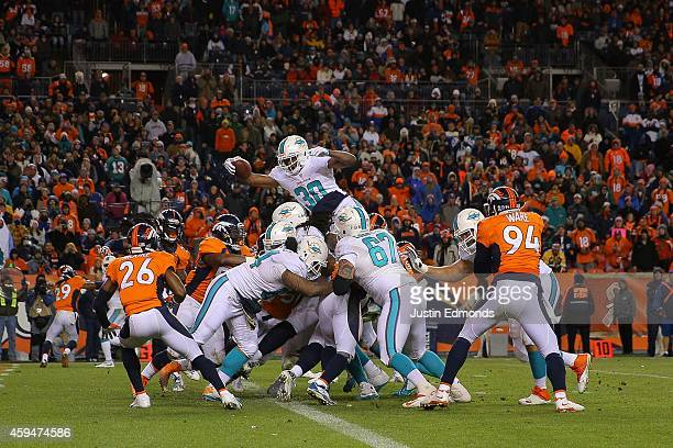 Running back Daniel Thomas of the Miami Dolphins leaps and extends the ball over the goal line for a 2point conversion late in the fourth quarter of...