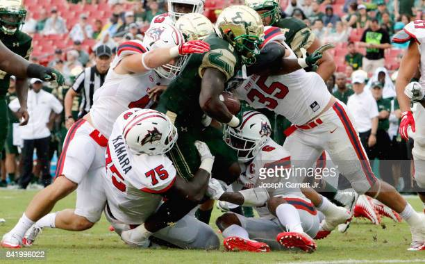 Running back Darius Tice fights for yardage against the Stony Brook Sea Wolves' defenders at Raymond James Stadium on September 2 2017 in Tampa...