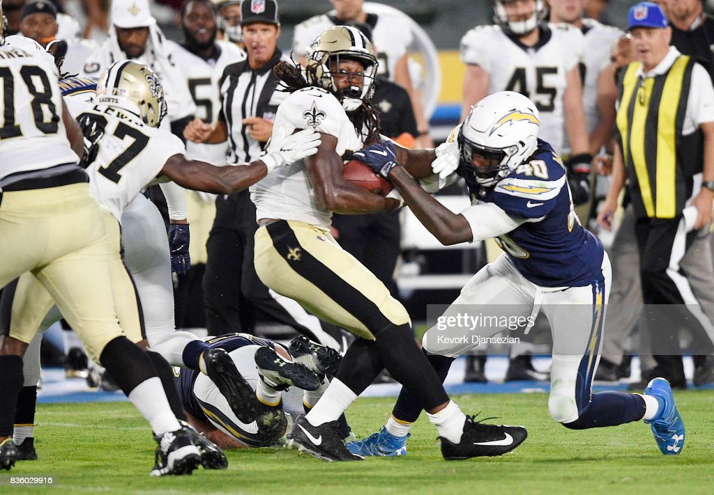 Running back Darius Victor #34 of the New Orleans Saints hangs on to the ball as defensive end Chris McCain #40 of the Los Angeles Chargers tries to strip it from him during the second half of a preseason football game against the New Orleans Saints at the StubHub Center August 20, 2017, in Carson, California.