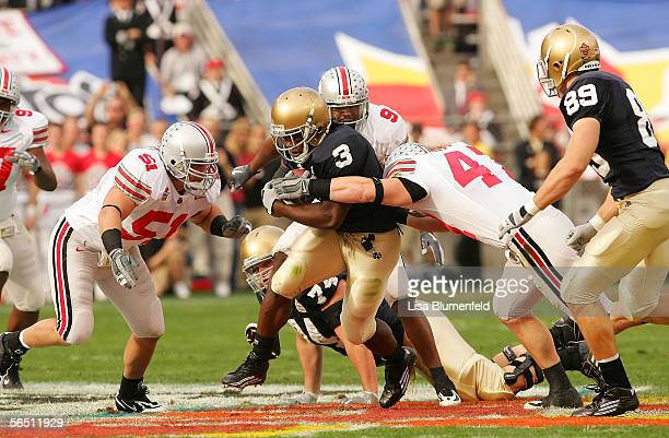 Running back Darius Walker of the Notre Dame Fighting Irish runs as linebakcer AJ Hawk of the Ohio State Buckeyes grabs him in the first quarter of...