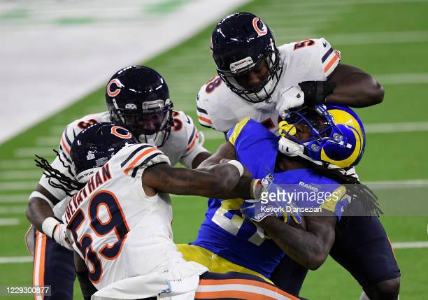 Running back Darrell Henderson of the Los Angeles Rams is tackled by inside linebacker Roquan Smith of the Chicago Bears during the second half at...