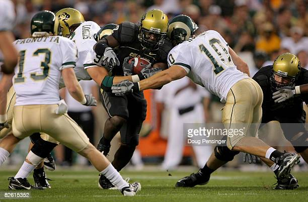 Running back Darrell Scott of the University of Colorado Buffaloes rushes as Jeff Horinek and Wade Landers of the Colorado State University Rams make...