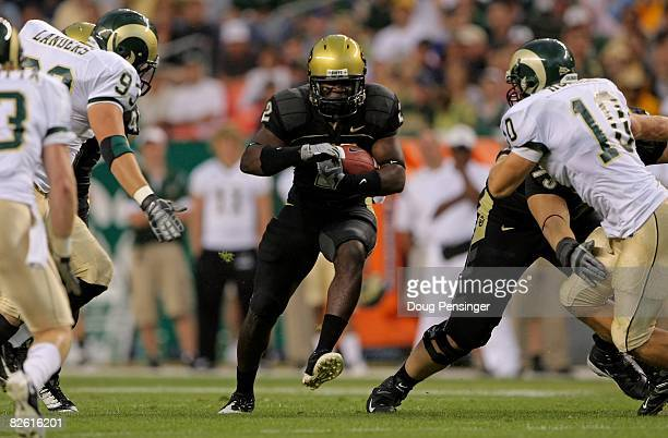 Running back Darrell Scott of the University of Colorado Buffaloes rushes as Jeff Horinek and Wade Landers of the Colorado State University Rams...