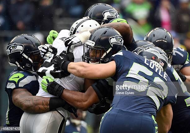 Running back Darren McFadden of the Oakland Raiders is gang tackled by outside linebacker Bruce Irvin, linebacker K.J. Wright and middle linebacker...