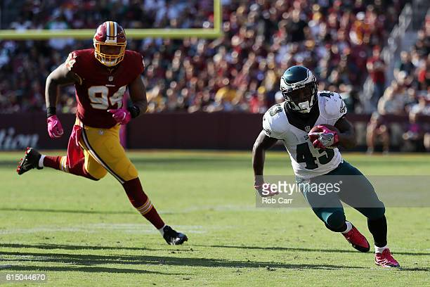 Running back Darren Sproles of the Philadelphia Eagles carries the ball past outside linebacker Preston Smith of the Washington Redskins in the...