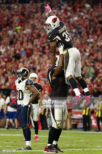 Running back David Johnson of the Arizona Cardinals is hoisted up by guard Jonathan Cooper after Johnson scored a 23 yard touchdown reception against...