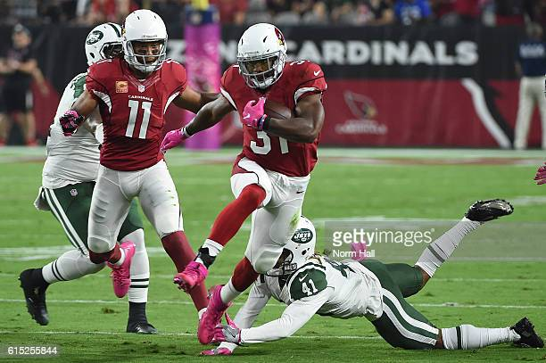 Running back David Johnson of the Arizona Cardinals jumps over cornerback Buster Skrine of the New York Jets then runs the football 58 yards to score...