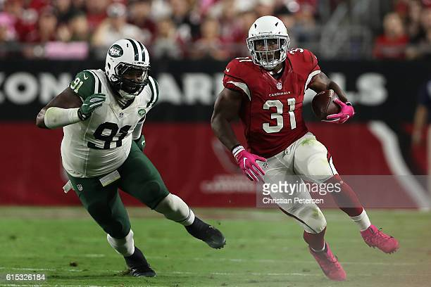 Running back David Johnson of the Arizona Cardinals runs with the football past defensive end Sheldon Richardson of the New York Jets after a...