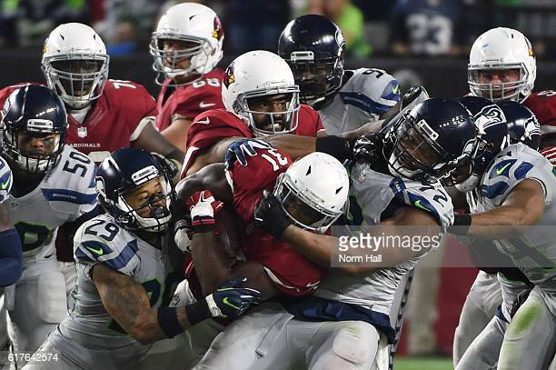 Running back David Johnson of the Arizona Cardinals rushes the football against free safety Earl Thomas and defensive end Michael Bennett of the...