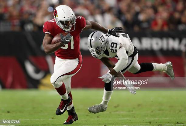 Running back David Johnson of the Arizona Cardinals rushes the football past cornerback David Amerson of the Oakland Raiders during the first half of...