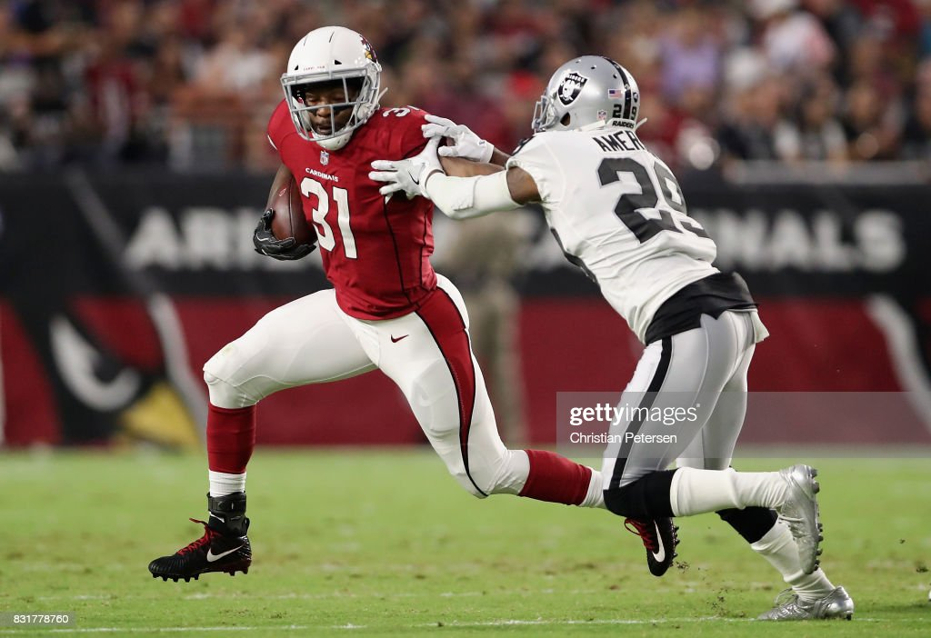 Running back David Johnson #31 of the Arizona Cardinals rushes the football past cornerback David Amerson #29 of the Oakland Raiders during the NFL game at the University of Phoenix Stadium on August 12, 2017 in Glendale, Arizona. The Cardinals defeated the Raiders 20-10.