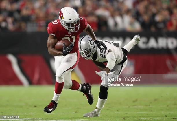 Running back David Johnson of the Arizona Cardinals rushes the football past cornerback David Amerson of the Oakland Raiders during the NFL game at...