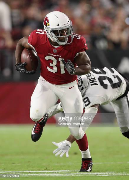 Running back David Johnson of the Arizona Cardinals rushes the football past cornerback David Amerson of the Oakland Raiders during the NFL game at...