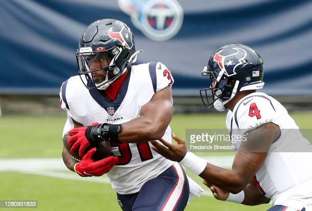 Running back David Johnson of the Houston Texans takes the hand off from quarterback Deshaun Watson in the first quarter against the Tennessee Titans...