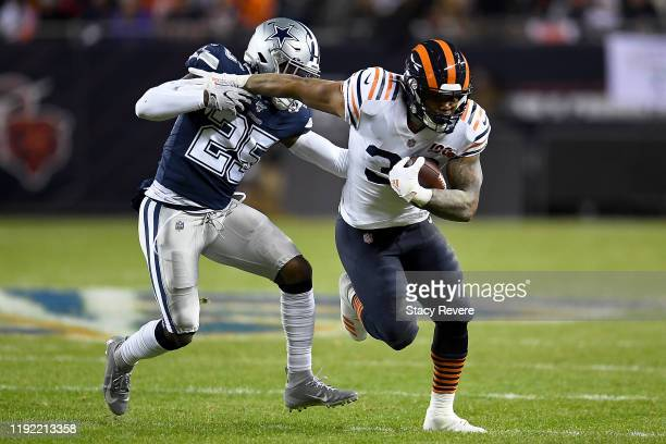 Running back David Montgomery of the Chicago Bears is tackled by free safety Xavier Woods of the Dallas Cowboys during the game at Soldier Field on...