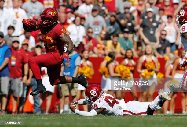 Running back David Montgomery of the Iowa State Cyclones breaks away from defensive back Brendan RadleyHiles of the Oklahoma Sooners while rushing...