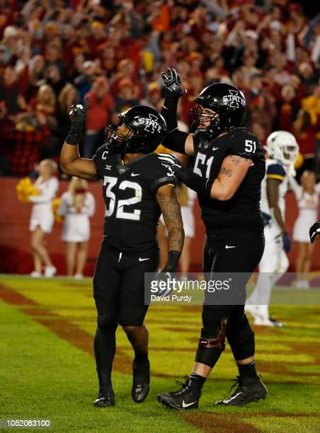 Running back David Montgomery of the Iowa State Cyclones celebrates after scoring a touchdown with teammate offensive lineman Julian GoodJones of the...
