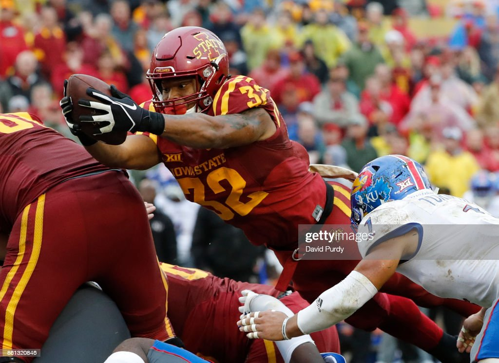 Running back David Montgomery #32 of the Iowa State Cyclones dives into the end zone for a touchdown as safety Bryce Torneden #1 of the Kansas Jayhawks blocks in the first half of play at Jack Trice Stadium on October 14, 2017 in Ames, Iowa.