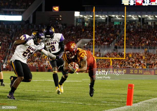 Running back David Montgomery of the Iowa State Cyclones drives into the end zone for a touchdown as defensive back Nikholi Jaghai of the Northern...